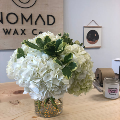 Nomad Candle Studio - white flowers in front of wood sign with Nomad logo