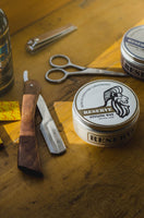 A can of Canadian-made RESERVE Styling wax sits on a table with razors and other men's grooming tools.