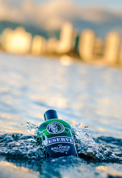 King & Country Grooming's RESERVE Daily Mint Shampoo splashing in the ocean with Vancouver in the distance.