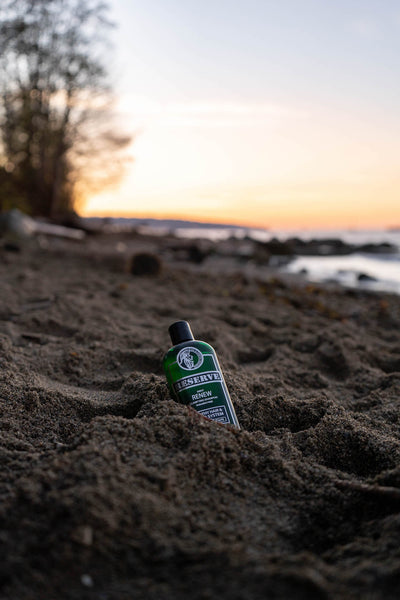 King & Country Grooming's RESERVE Clarifying Mint Shampoo sits in the sand on the beach of Vancouver - Made in Canada