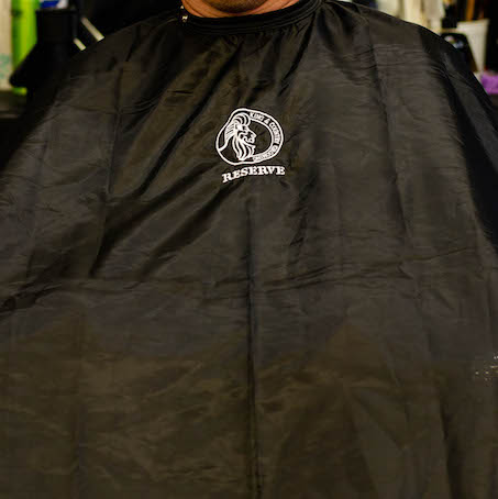 Black cutting cape from King & Country Grooming RESERVE men's hair styling products.