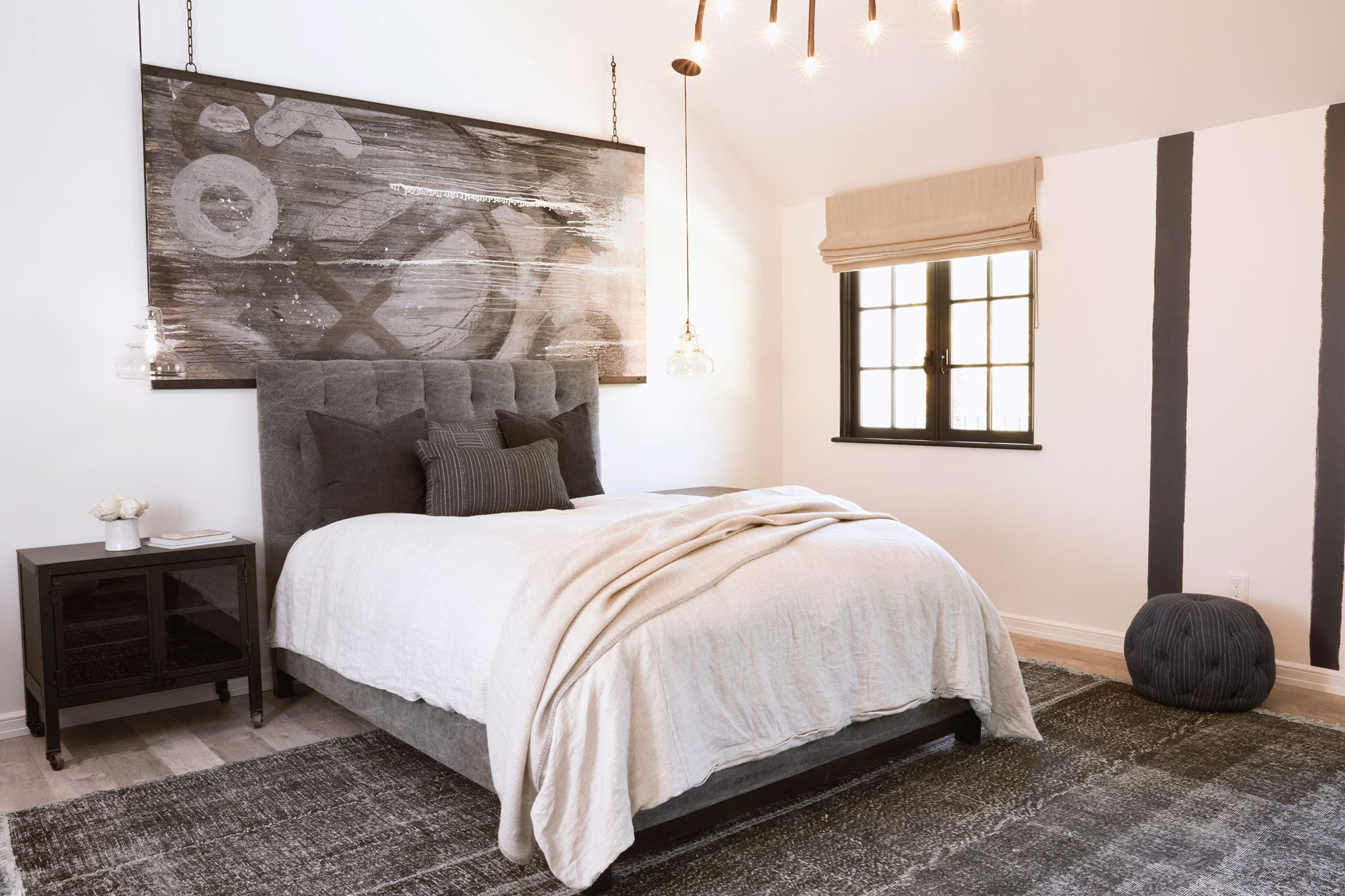 bed in light filled room and pendant glass lighting