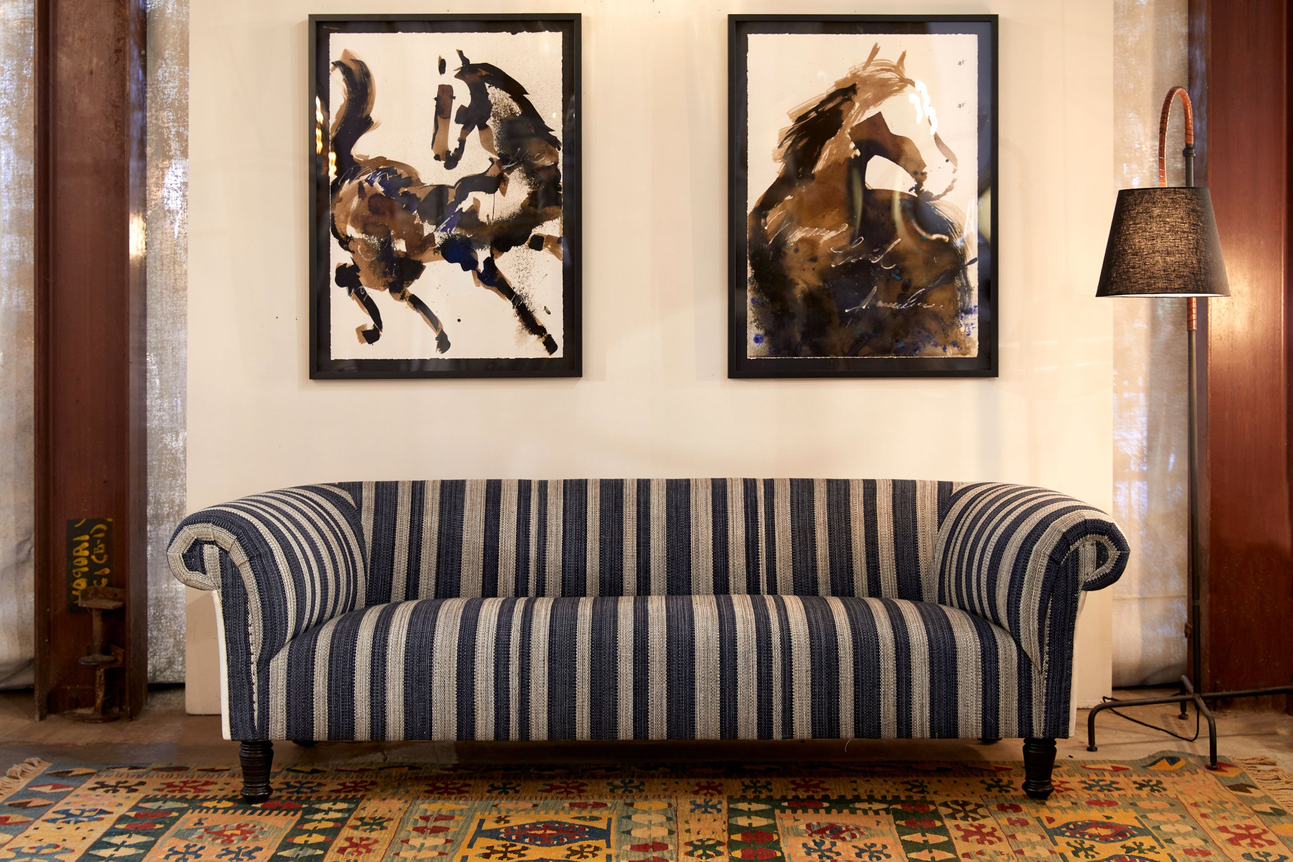 sofa in striped fabric with two painting on the wall behind the sofa
