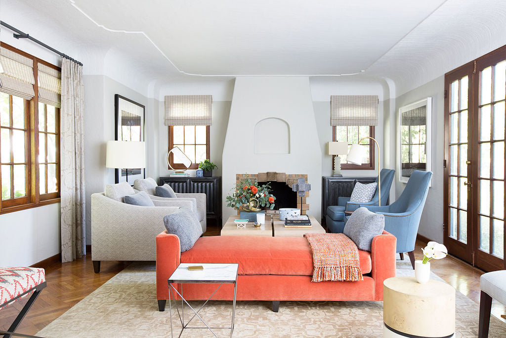 light filled living room interior featuring salmon colored daybed two grey lounge chair and two light blue club chairs in front of a fireplace