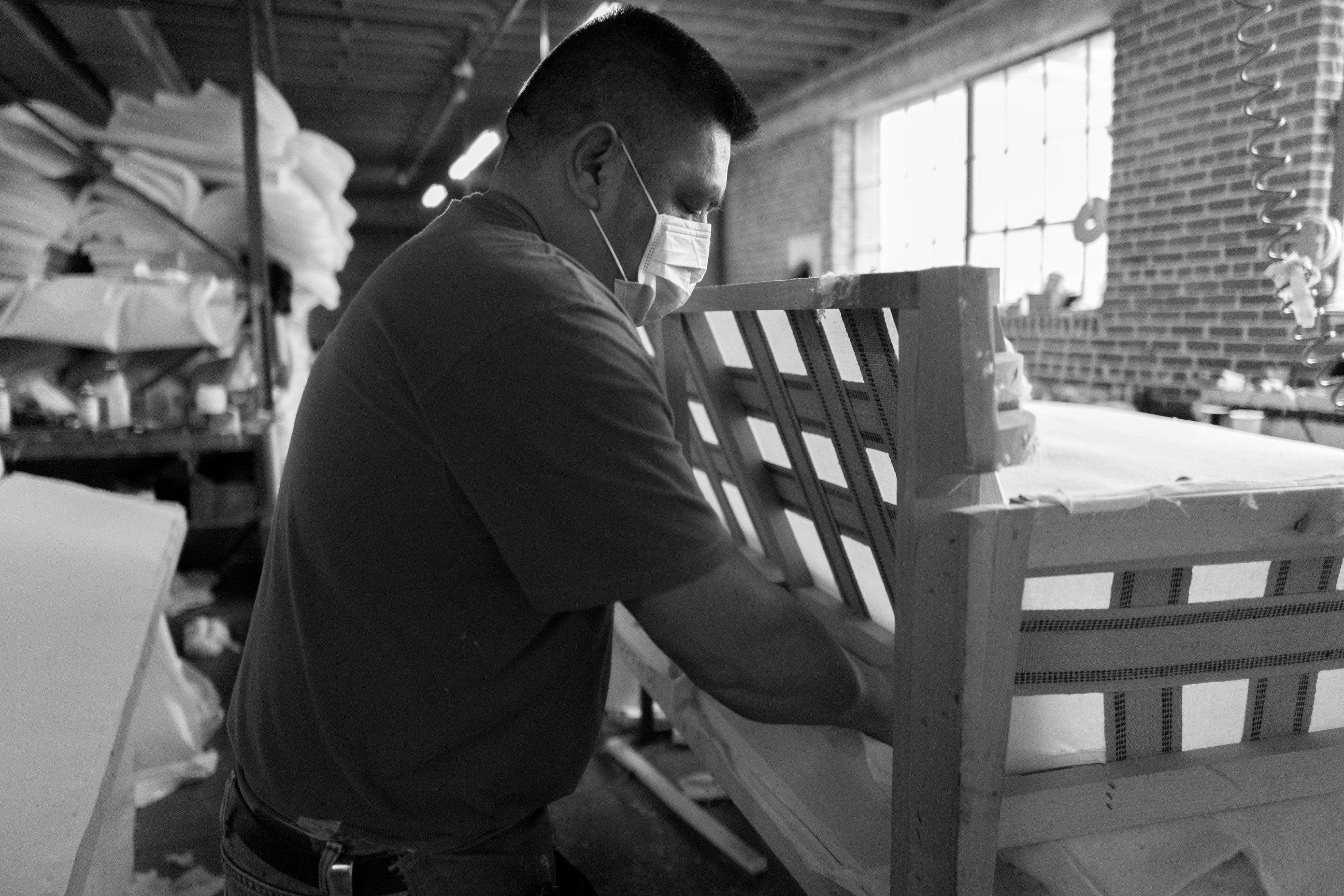 black and white image of a Craftsman working on sofa