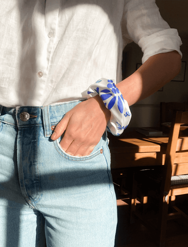 Lio Mara Blue Floral Silk Scrunchie Worn On Wrist With Blue Jeans