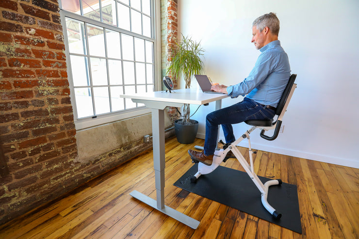 Man Riding FitDesk Standing Desk Bike at home