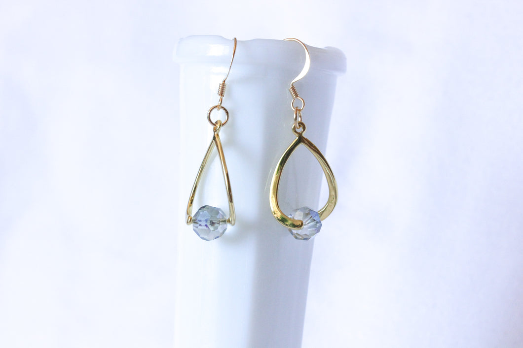 Curvy earrings - gold with round smoky blue crystal