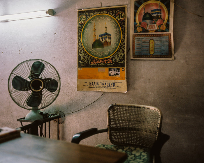 """Office Desk"" an inkjet print by Saleem Ahmed. depicts an sparsely furnished office with two colorful posters on the wall. Cityscape, fan, office, urban landscapes. The Print Center"