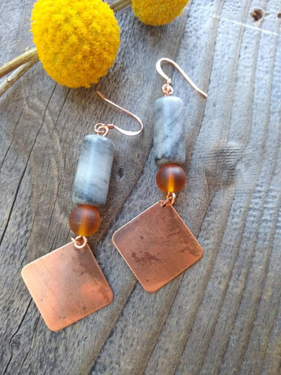 Copper and stone dangle earrings. Diamond shaped copper dangles with marbled grey and white stones and coppery toned glass bead earrings.