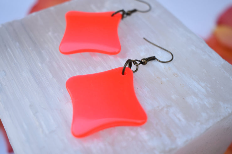 Vibrant orange star earrings.