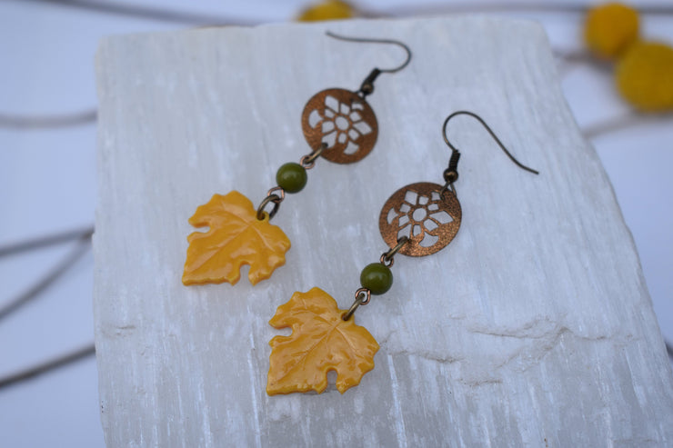 Delicate leaf and brass chain dangle earrings. Yellow acrylic leaves and floral cut out accents, boho dangle earrings