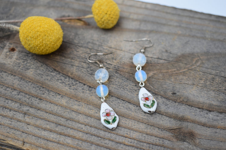 Sweet mid length white enameled floral beads and round opalescent glass beads.