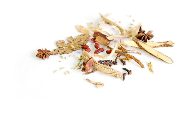 Pieces of astragalus root spread over a white background