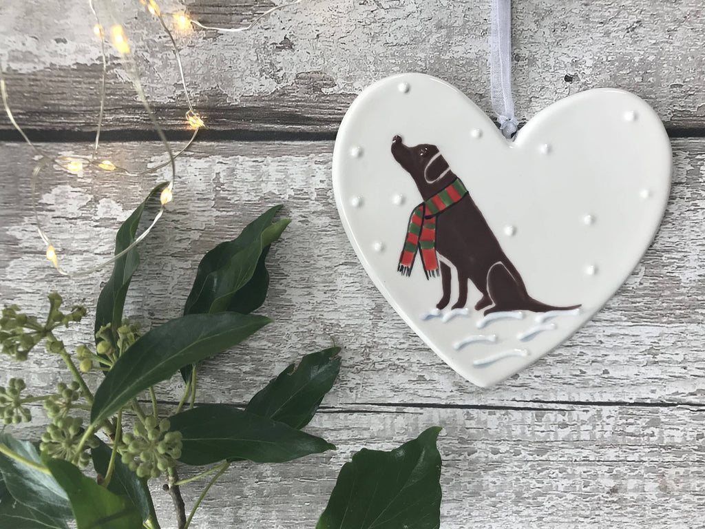 Chocolate Labrador Wearing A Red And Green Striped Scarf Sitting Down In The Snow Hand Painted Christmas Ceramic Heart