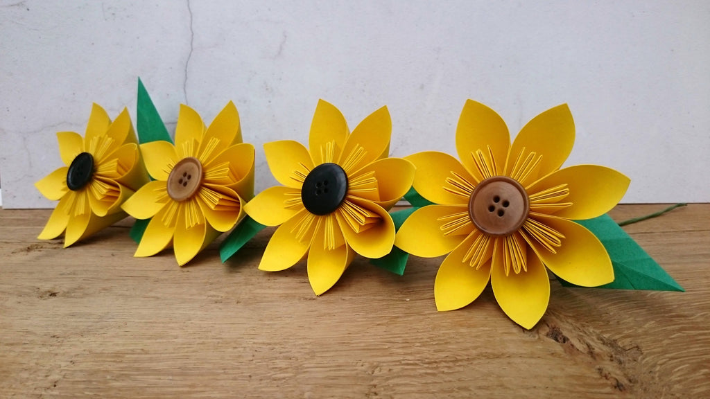 Yellow origami paper sunflower with green leaves