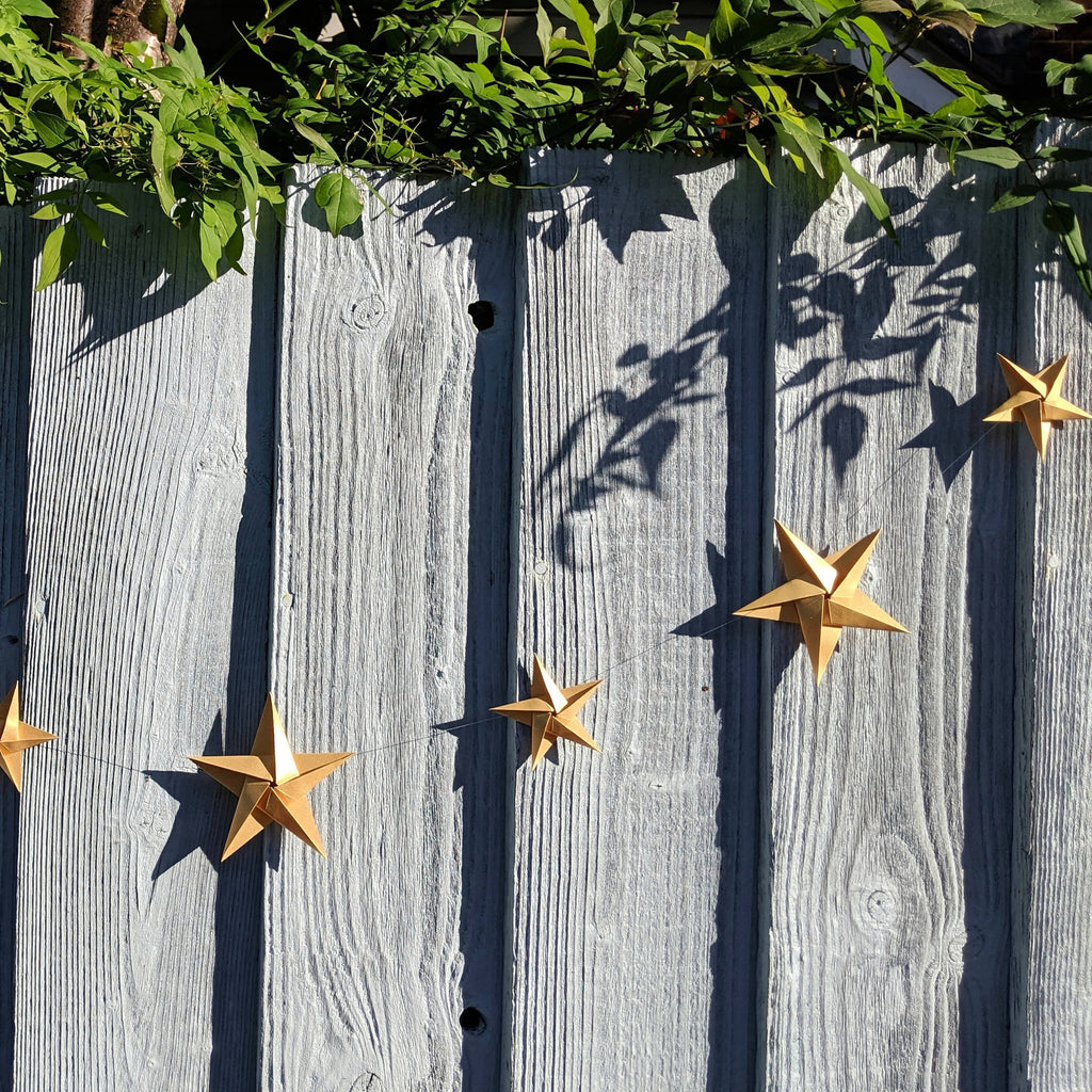 gold origami star bunting hanging on fence in sunshine