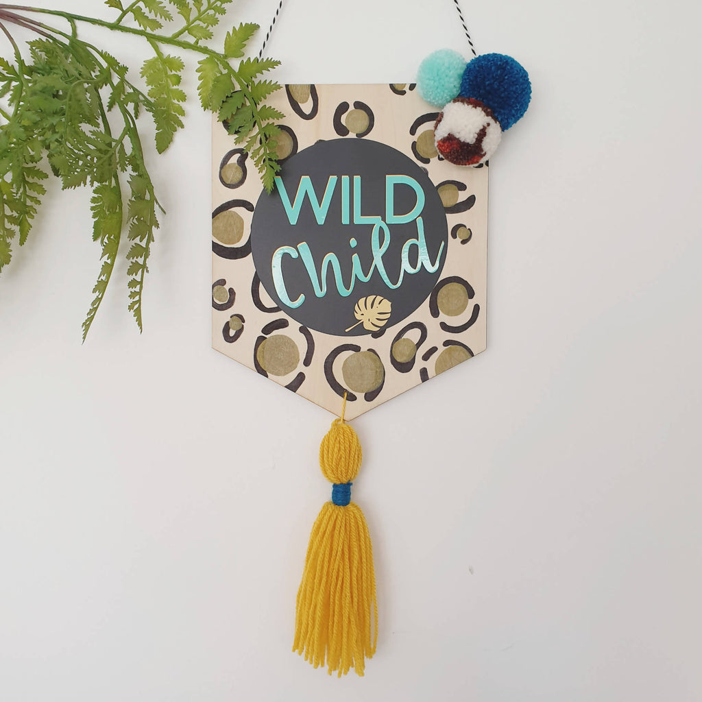 Wild child wooden banner with tassel and pom poms