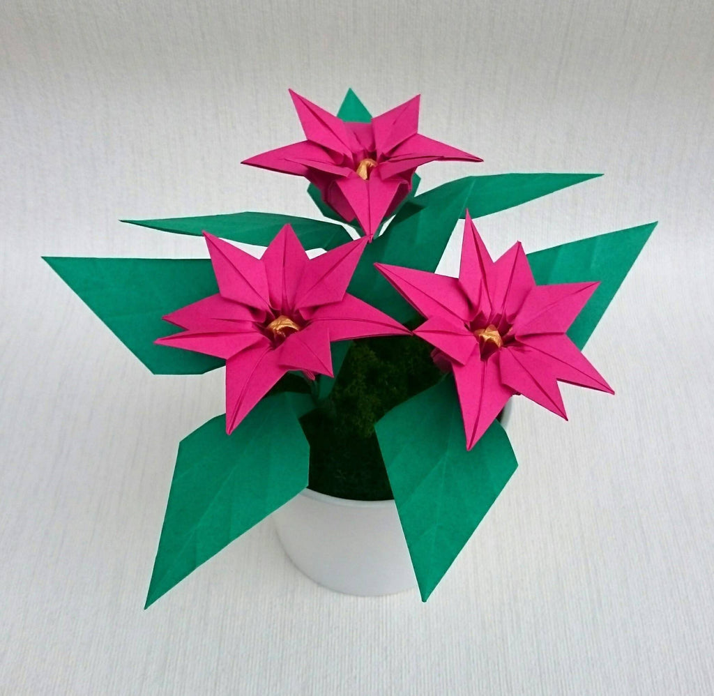 Pink origami poinsettia plant in white ceramic pot