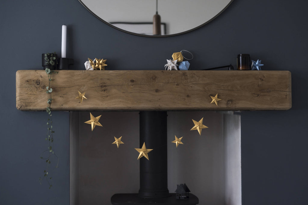 gold paper star garland hanging across fireplace