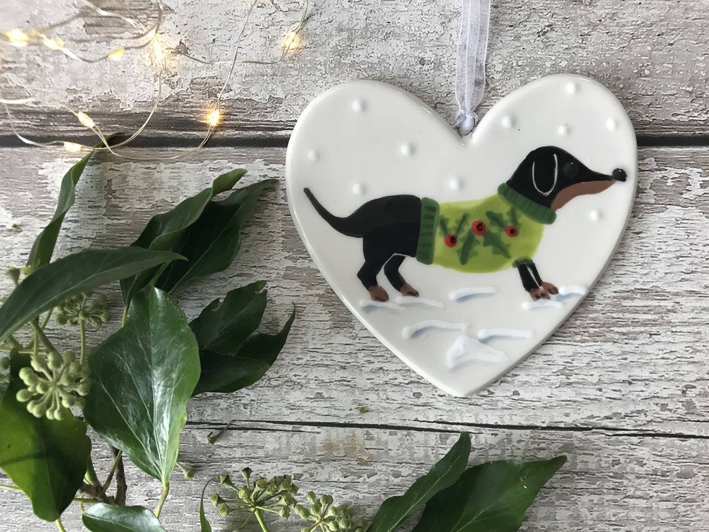 Black and Tan Dachshund / Sausage Dog Wearing A a Green Christmas Jumper Standing In The Snow Hand Painted Christmas Ceramic Heart