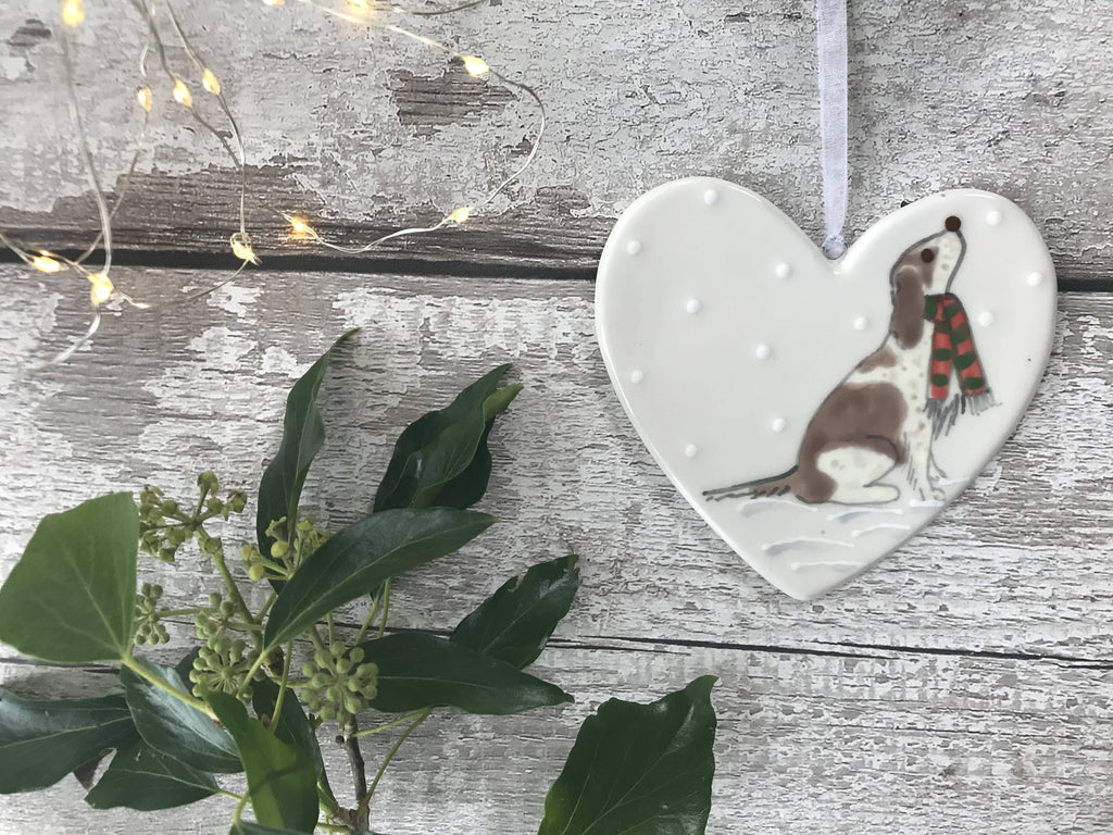 Brown And White Spaniel/Cockapoo Wearing A Red And Green Striped Scarf Sitting Down In The Snow Hand Painted Christmas Ceramic Heart
