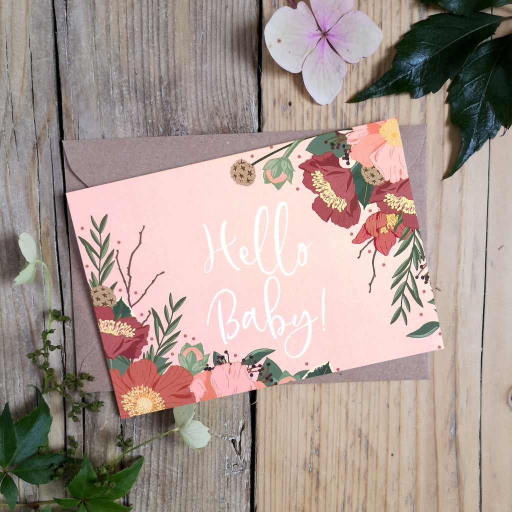 A beautifully illustrated Hello Baby card on a blush pink background filled with Autumnal blooms.