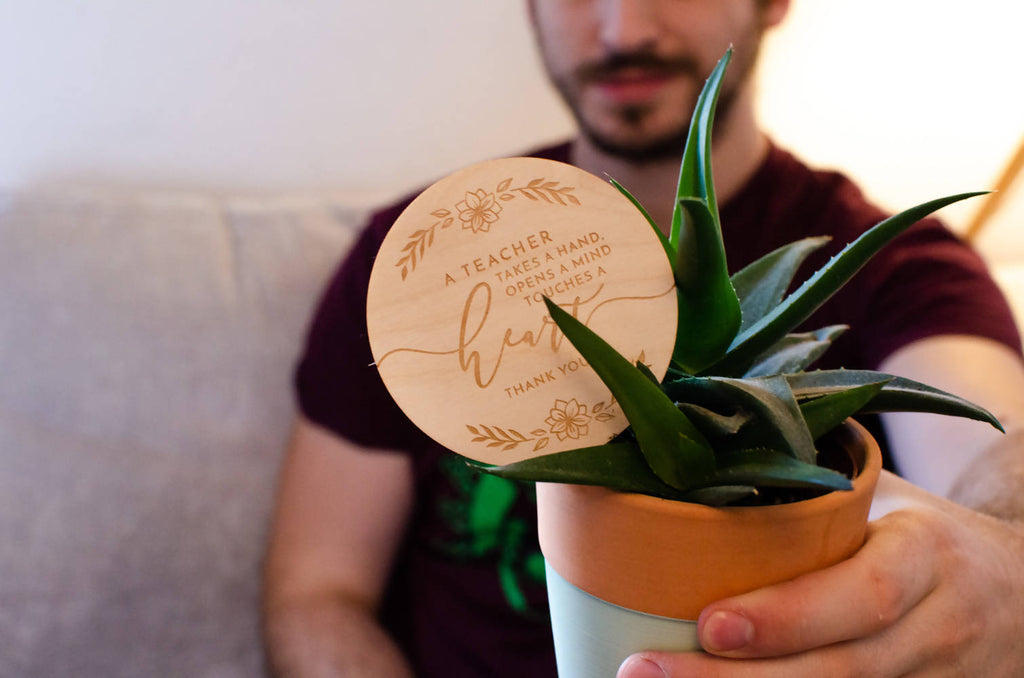 A teacher touches a heart engraved wooden plant topper