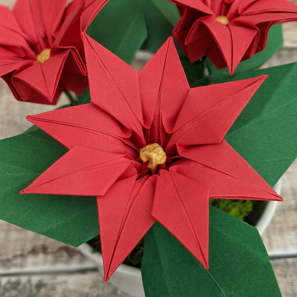 Red origami poinsettia plant in ceramic pot