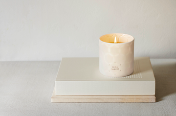 Photo of white isle de nature candle on top of a beige book