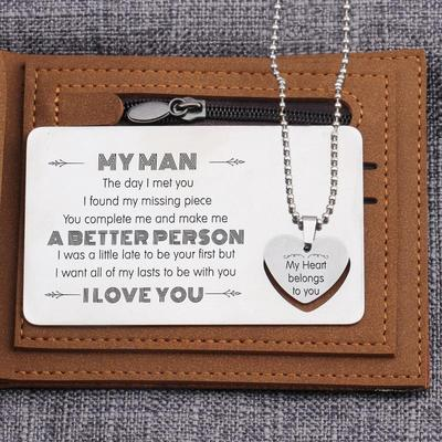 Engraved wallet card and heart necklace set on top of a wallet