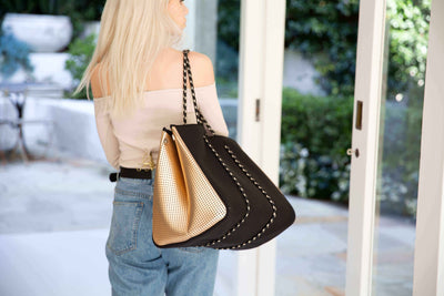 Back of girl holding Mikah chuchka neoprene bag in black gold