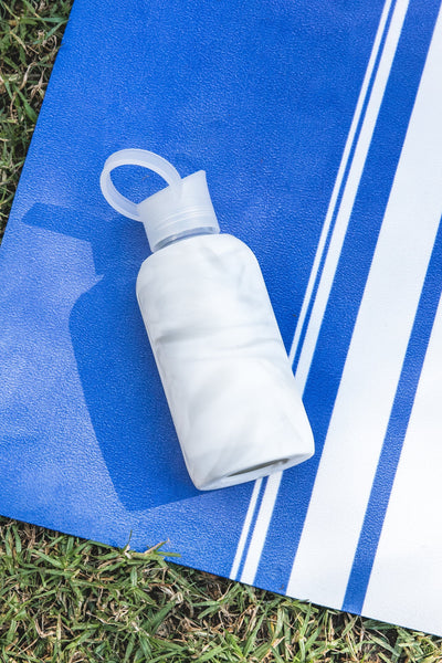 Eco friendly glass water bottle on Prana Suede Yoga Mat