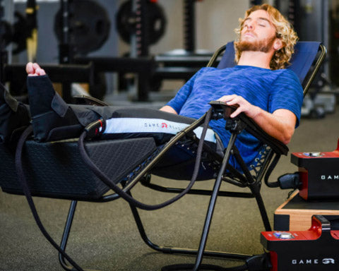 Game Ready GRpro 2.1 Cold Compression unit in use by model laying in zero-gravity chair