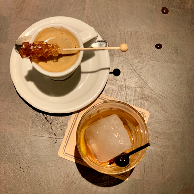 espresso with brown sugar in white cup on white dish next to brown liquor old fashioned in glass with black cherry on wood table