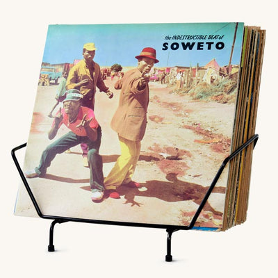 "A black record rack displaying the album ""The Indestructible Beat of Soweto""."