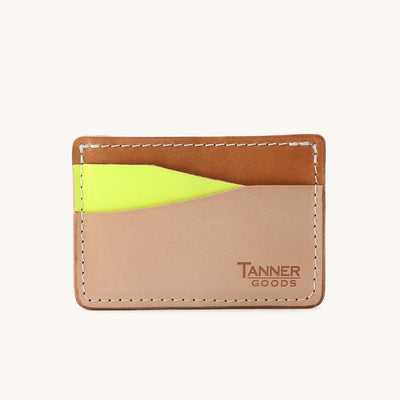A multicolored leather card wallet in natural, tan, and neon yellow.