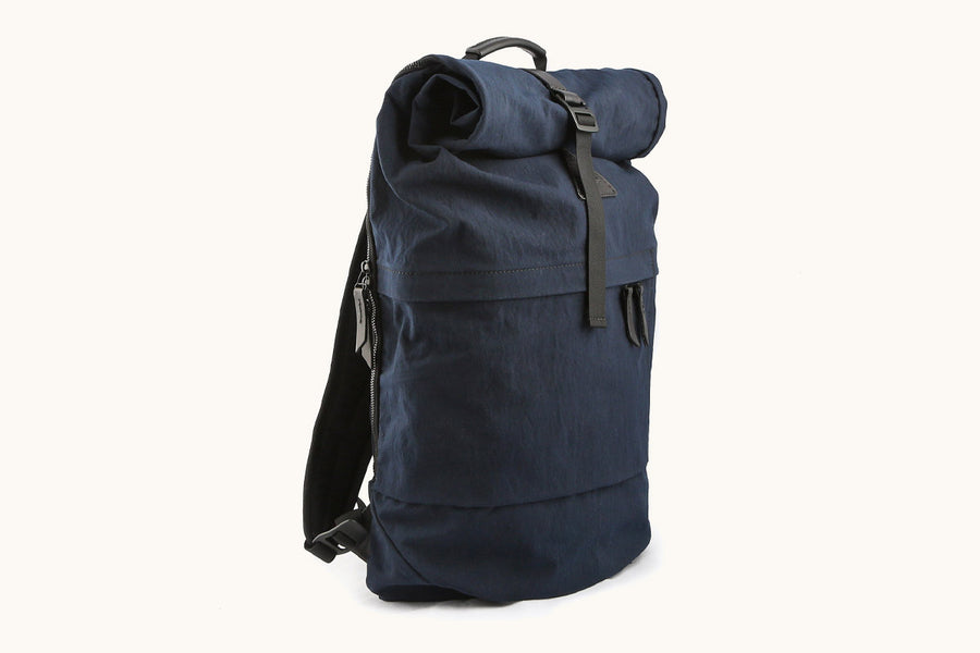 A navy blue roll top backpack with black accents with front and side pockets.