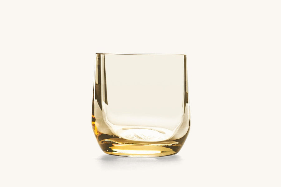 A cocktail glass with a slight yellow hue in the glass.