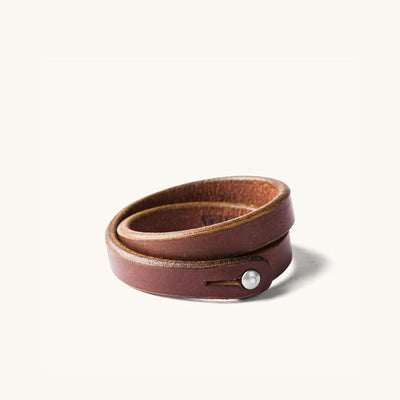 A double wrap brown leather wristband with metal closure.