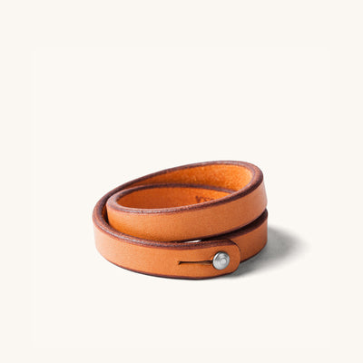 A double wrap tan leather wristband with metal closure.