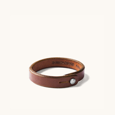 Brown leather wristband with metal rivet closure.