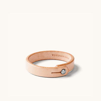 Natural leather wristband with metal rivet closure.