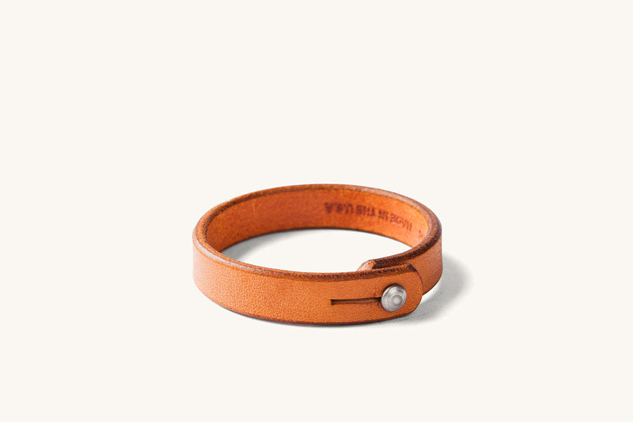 Tan leather wristband with metal rivet closure.