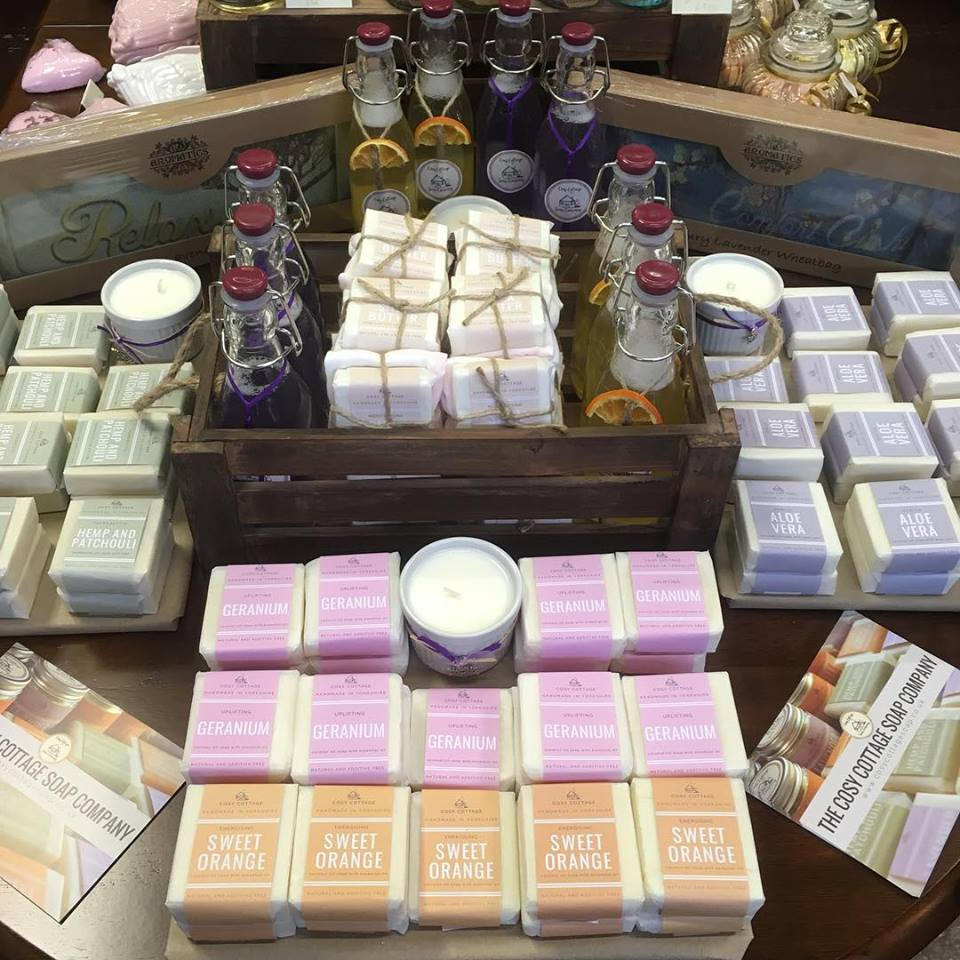 stacks of handmade soaps and candles in a wooden crate