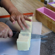 natural soap bar being cut by hand with a knife