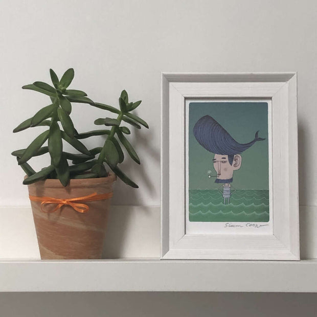 framed cooperillo picture of a whale haircut on a shelf next to a pot plant