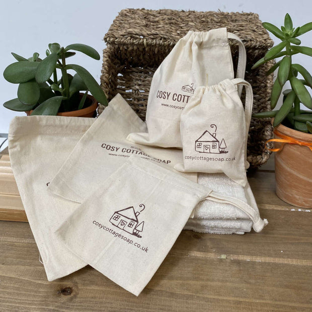 cosy cottage natural cotton drawstring soap bags filled stacked on empty soap bags and cotton face coth