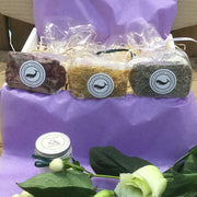 three soap bundles with petals in lined up on gift box