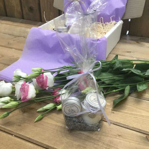 handmade candle and lip balm bundle surrounded by flowers